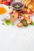café da manhã - croissants com straberry, framboesa e amora, chá, geléia foto