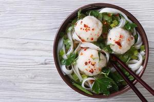 sopa asiática com bolinhas de peixe e macarrão de arroz vista superior foto