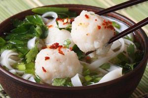 sopa asiática tradicional com bolinhas de peixe e pauzinhos foto