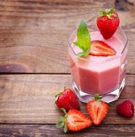 beber smoothies verão morango, amora, framboesa na mesa de madeira foto
