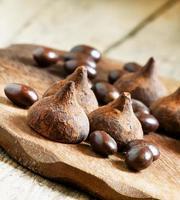 trufas de chocolates e bolas em um fundo de madeira foto