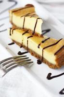 cheesecake com calda de chocolate em um prato branco sobre fundo branco traseiro foto