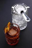 cocktail à moda antiga negroni perto de copo com gelo no foto