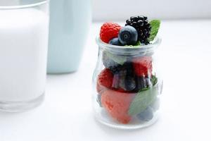 frutas e hortelã na jarra e copo de leite