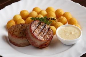deliciosa carne grelhada com molho e bolinhas de queijo foto
