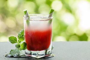 cocktail vermelho congelado com hortelã no terraço