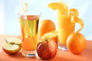 copos de suco de laranja e maçã com batatas fritas inteiras foto