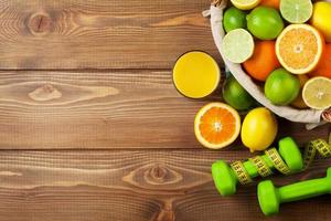 frutas cítricas na cesta e dumbells. laranjas, limas e limões