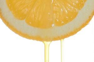 fatia de laranja com suco fluindo foto