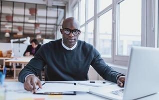 Africano jovem bonito em sua mesa com o laptop foto