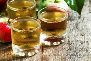 suco de maçã frio e maçãs frescas foto