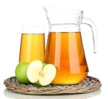 copo cheio e jarra de suco de maçã isolted em branco foto