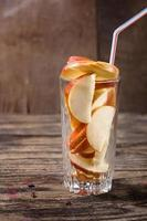 copo com fatias de maçãs foto