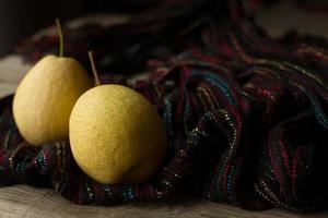 pêra com maçãs em um fundo marrom foto