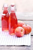 garrafas com bebidas vermelhas e algumas maçãs foto