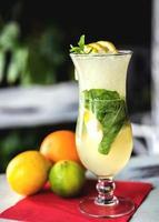 limonada suave de limão verde fresco em um copo na madeira foto