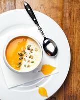 sopa de abóbora com creme e sementes em uma tigela branca foto