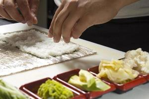fazendo rolo de sushi foto