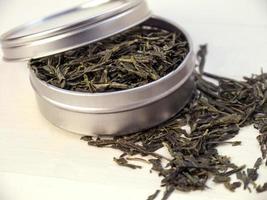chá verde em lata de prata foto