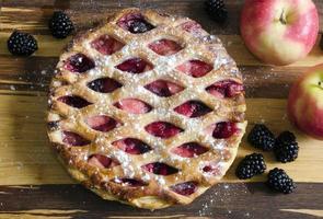 torta de maçã com frutas na mesa de madeira