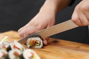 faca de sushi mestre fatiar rolos de sushi foto