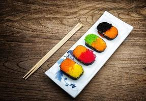 sushi colorido em fundo de madeira