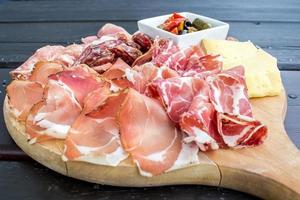 aperitivo italiano típico com salame, queijo e picles foto