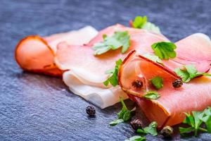enroladas fatias de presunto delicioso com folhas de salsa foto