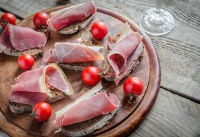 sanduíches com presunto italiano na placa de madeira