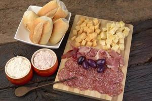 charcutaria e prato de queijos, pão, azeitonas e bolinhos foto