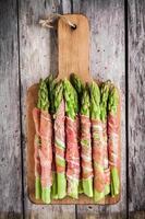 aspargos orgânicos frescos envoltos em presunto em uma placa de corte foto