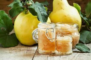 geléia de marmelo rosa em potes de vidro e marmelo fresco
