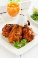 pernas de frango assado com molho barbecue e chutney de manga.