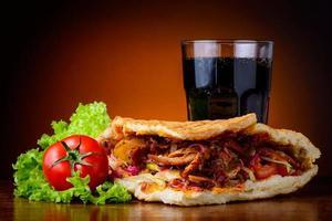 kebab, legumes e bebida de cola foto