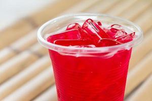 refrigerantes em copos de plástico na mesa de bambu foto