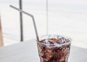 copo de cola com cubos de gelo foto