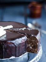 corte um bolo de chocolate com creme de manteiga e cerejas, feriado foto