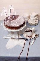 bolo festivo com cobertura de chocolate na mesa servida louça branca foto