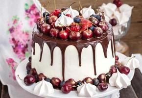 bolo decorado com chocolate, merengues e frutas frescas
