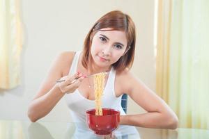jovem comendo macarrão ramen foto