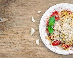 prato de macarrão com tomate e manjericão foto