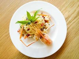 macarrão espaguete italiano e molho de camarão picante fresco na madeira foto