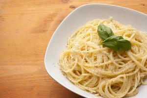 espaguete com queijo parmesão e manjericão em um prato foto