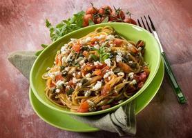 espaguete com tomate alcaparras de queijo e rúcula foto