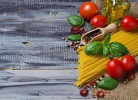 comida italiana macarrão, tomate, manjericão, azeite, pimenta foto