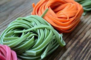 macarrão italiano cru colorido na mesa de madeira