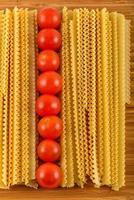 macarrão italiano espaguete e tomate cereja isolado na bac de madeira foto