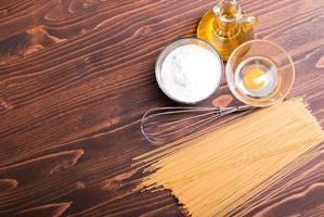 macarrão cru com especiarias e ingredientes marrom mesa de madeira foto