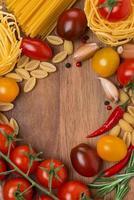 macarrão, temperos e tomate cereja em uma placa de madeira foto