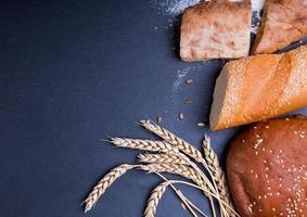diferentes tipos de pão e espigas de trigo foto